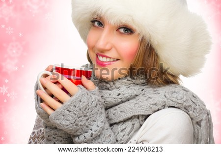 Young smiling girl with mug on winter background - stock photo