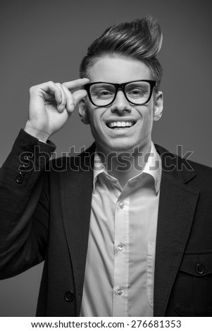 Young  smiling handsome man in glasses and tuxedo posing in the studio. Black and white fashion portrait. - stock photo