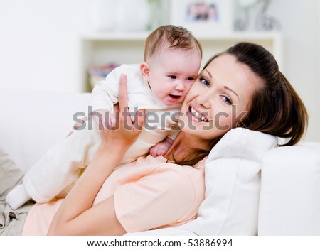 Young smiling happy mother with little baby on the sofa - indoors - stock photo