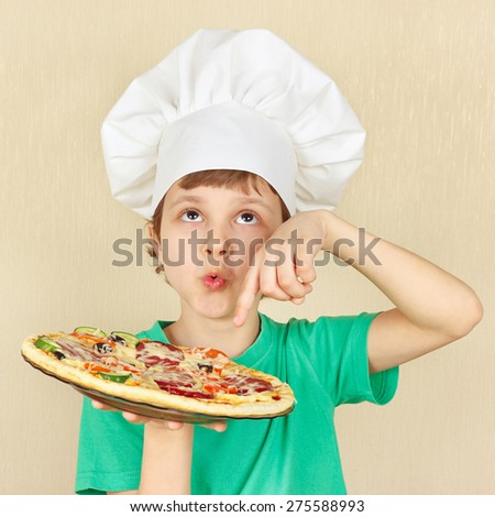 Young smiling kid in chefs hat with a cooked appetizing pizza - stock photo