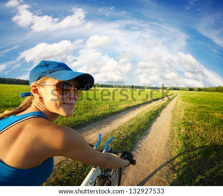 Young smiling lady cycling on a countryside road at summer sunny day - stock photo