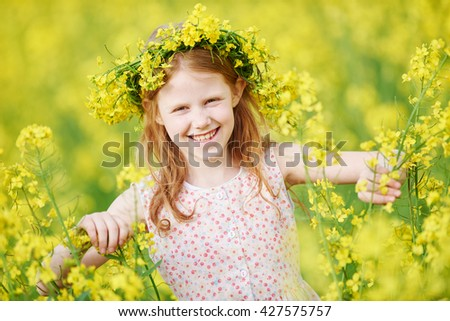 young smiling little girl with flower garland at yellow green rape seed meadow expressing joy - stock photo