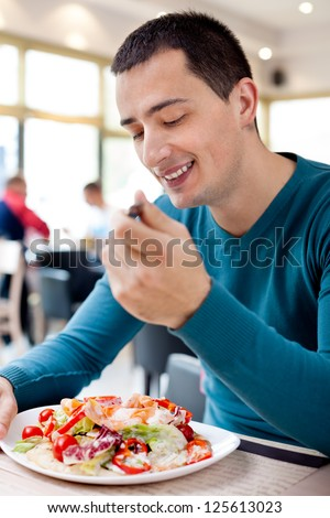 Young smiling man eating at restaurant - stock photo