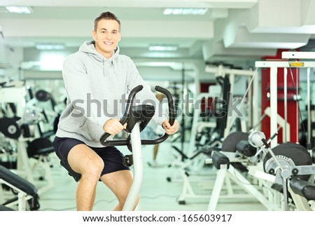 Young smiling man in a gym, exercising his legs doing cardio training - stock photo