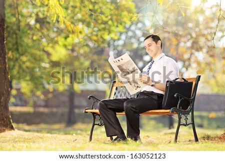 Young smiling man seated on a wooden bench reading a newspaper in a park - stock photo