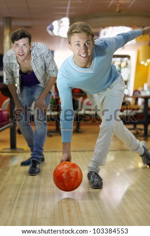 Young smiling man throws ball in bowling; friend looks at aim; shallow depth of field - stock photo