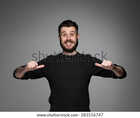 young smiling man with a beard and mustache in black pointing himself on a gray background - stock photo