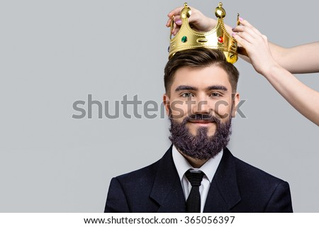 Young smiling man, with violet beard and eyebrows, wearing in dark blue suit and tie, posing when girls hands holding crown over his head, on white background, in studio, close up - stock photo