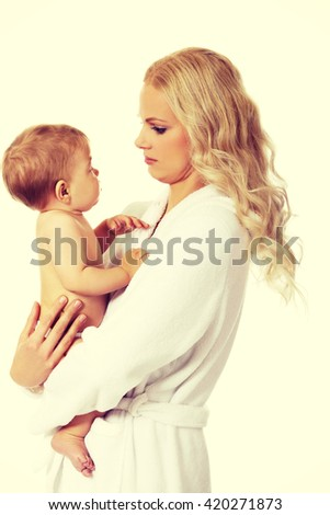 Young smiling mother in bathrobe holds her baby - stock photo