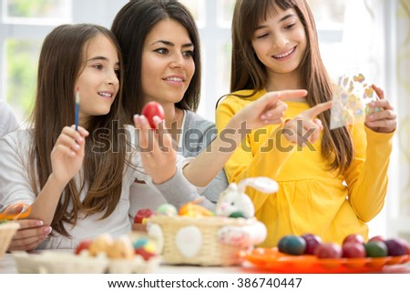 Young smiling mother   with two daughters  painting Easter eggs - stock photo