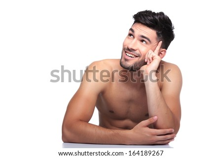 young smiling naked beauty man is looking up to his side on white background - stock photo