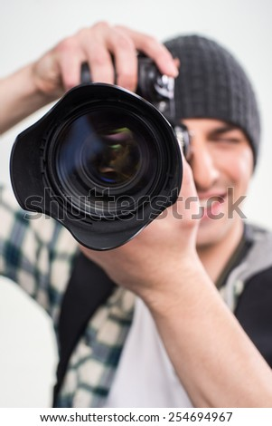 Young smiling photographer is using professional camera on gray background. Close-up. - stock photo