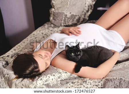 Young smiling pregnant woman with cat at home. - stock photo
