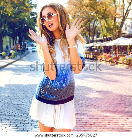 Young smiling pretty woman with bright make up and blonde fluffy hairs posing on the street at nice sunny summer day. Wearing sparkled sweater and sunglasses, surprised emotions. - stock photo