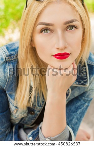 Young smiling pretty woman with bright make up and blonde fluffy hairs posing on the street at nice sunny summer day. - stock photo