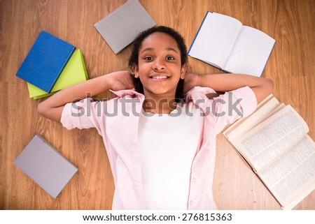 Young smiling schoolgirl laying on the floor with some color books. - stock photo