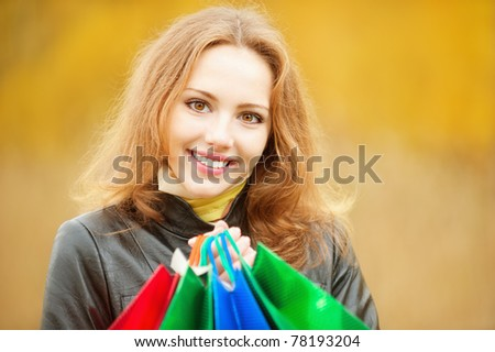 Young smiling student with purchases in packages comes from shop against yellow autumn nature. - stock photo