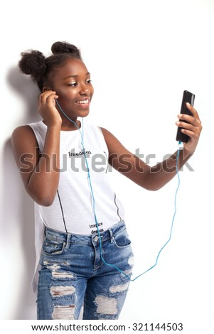 Young smiling teenage girl listening to music from mobile phone. African american girl. Studio shot. - stock photo