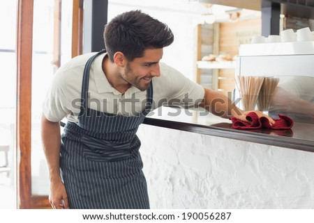 Young smiling waiter cleaning countertop with sponge - stock photo