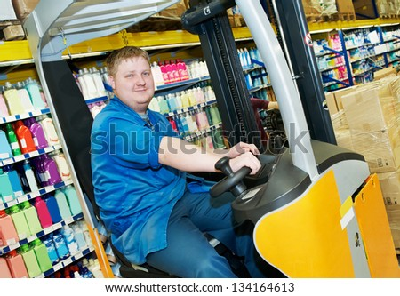 young smiling warehouse worker driver in uniform in forklift stacker loader in supermarket - stock photo