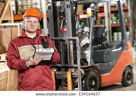 young smiling warehouse worker driver in uniform in front of forklift stacker loader - stock photo