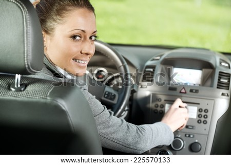 Young smiling woman adjusting radio volume in the car. - stock photo