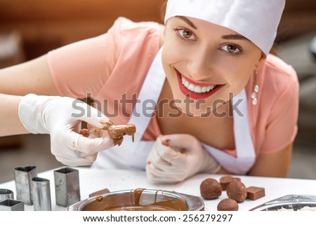 Young smiling woman chef dressed in white pinafore making handmade chocolate candy in the cafe - stock photo