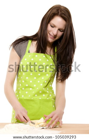 young smiling woman cutting butter or shortening for baking on white background - stock photo