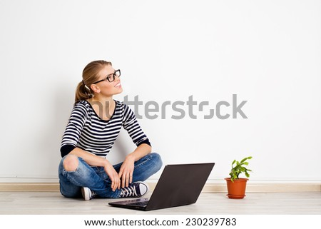 Young smiling woman dreaming of new home decor and furniture. Pretty Caucasian female sitting with laptop at white wall in empty room of new bought apartment.  - stock photo