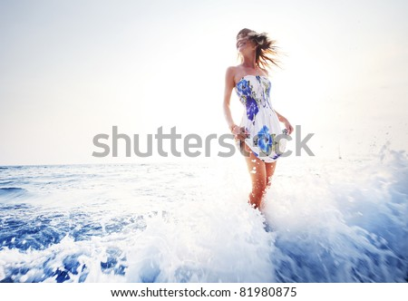Young smiling woman having fun standing in blue sea water - stock photo
