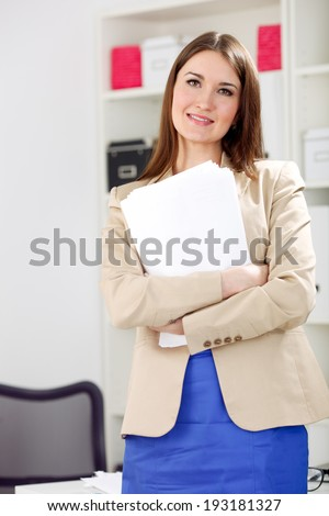 young smiling woman holding blank, paper in office - stock photo