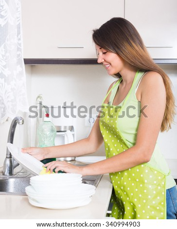 Young smiling woman in apron washing plates with sponge in domestic kitchen