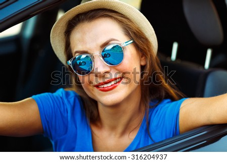 Young smiling woman in hat and sunglasses making self portrait sitting in the car - stock photo