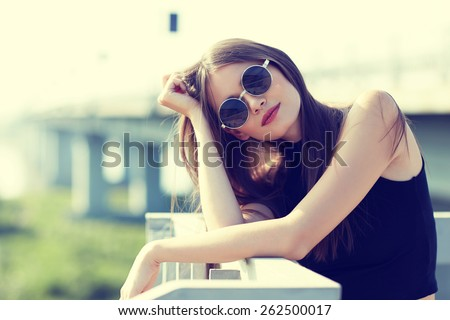 young smiling woman in sunglasses outdoor - stock photo