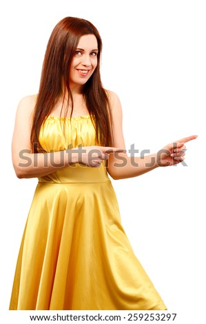 Young smiling woman in yellow dress point finger showing something to side empty copy space isolated on white background - stock photo