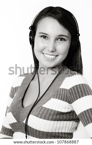 young smiling woman listening to music on her head phones - stock photo