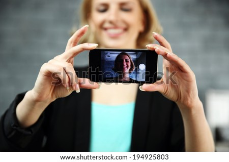 Young smiling woman making a self photo by her smartphone in office. Focus on smartphone - stock photo
