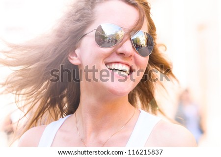 young smiling woman on bright city street - stock photo