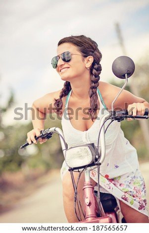 young smiling woman on scooter with sunglasses and braid hair - stock photo
