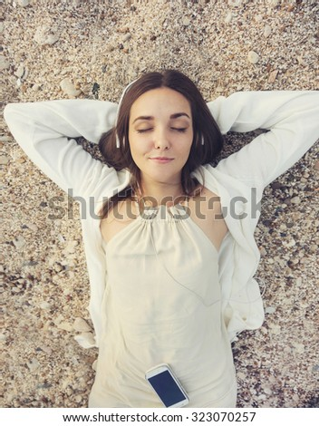 Young smiling woman outdoor portrait lying on a sea sand and listening music, top view. - stock photo
