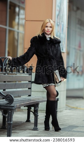 Young smiling woman outdoors portrait. Soft sunny colors.Close portrait. Winter portrait of a beautiful young blonde Caucasian girl with straight hair  outdoors in the city  - stock photo