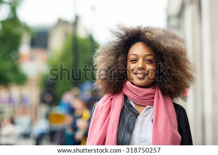 Young smiling woman portrait in the street in London. Filtered image. - stock photo