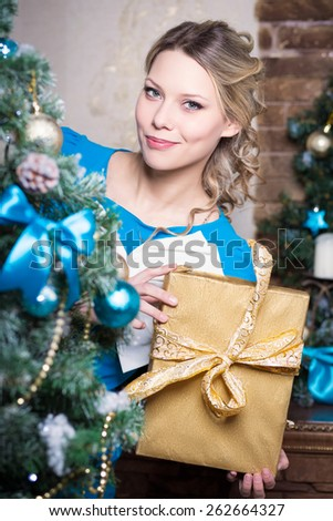 Young smiling woman posing behind the fir-tree with a golden gift box - stock photo