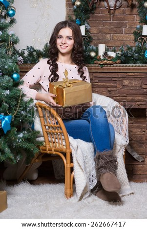 Young smiling woman posing with a golden gift box near the fireplace - stock photo