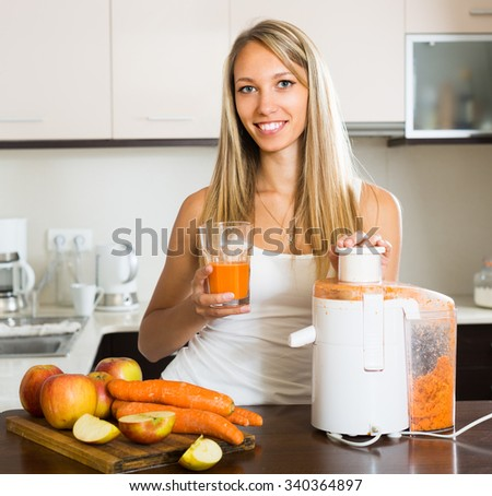 Young smiling woman preparing fresh juice in domestic kitchen - stock photo