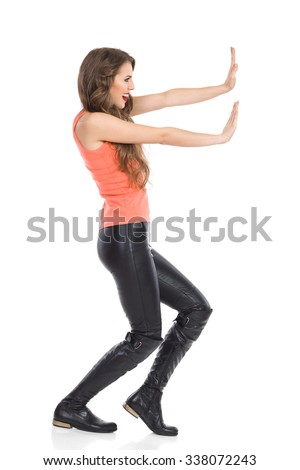 Young smiling woman pushing imaginary wall. Side view. Full length studio shot isolated on white. - stock photo