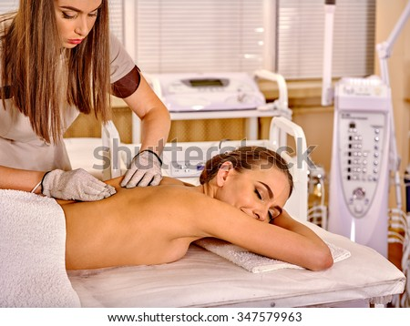 Young smiling woman  receiving electric massage at  hardware cosmetology beauty salon. Beautician wearing electricity gloves.  - stock photo