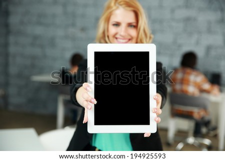 Young smiling woman showing blank tablet computer screen in office. Focus on tablet computer - stock photo