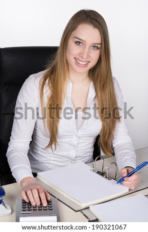 Young smiling woman sits at the desk in the office and works - stock photo