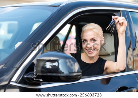 Young smiling woman sitting inside new car and showing keys to it. Concept for car rental - stock photo